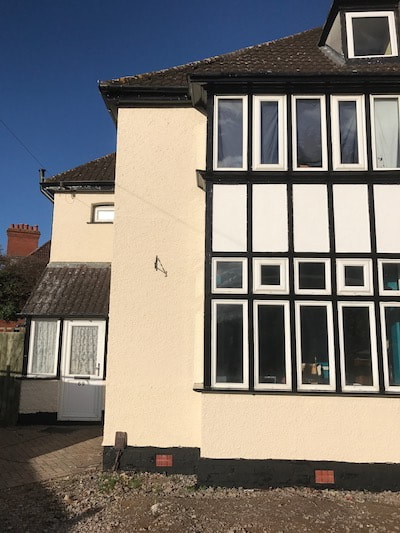 Photo of the front of a house with black and white windows that were painted by our decorators in Gloucester.