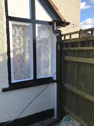 Photo of the side of a porch on a house with black and white windows that were painted by our decorators in Gloucester.