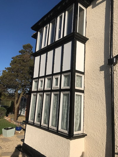 Photo of the side aspect of a house with black and white windows that were painted by our decorators in Gloucester.