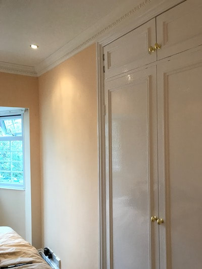 Painting and decorating in a Gloucester bedroom. A warm peach colour. Photo shows a lovely smooth finish on gloss work on a built in wardrobe.