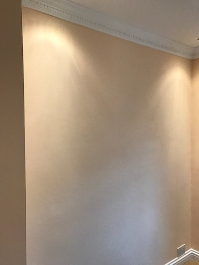 Painting and decorating in Gloucester. A warm peach colour. Photo shows a lovely even finish on one of the bedroom walls.